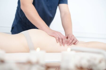 Portrait of a masseur male doing hip massage to a girl in a spa salon. Massage and body care concept