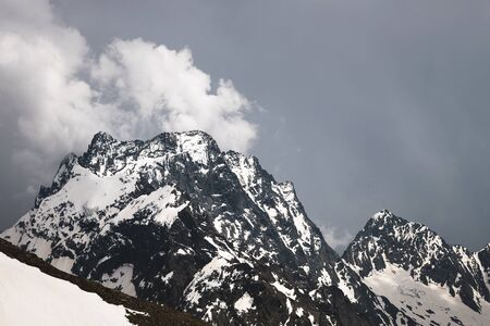 View of a high steep rocky mountain partially covered with snow against a dark cloudy sky with clouds clinging to the top. Mountain weather change concept