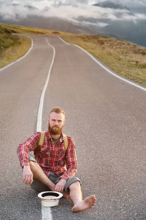 Stylish barefoot bearded male hitchhiker traveler in a hat and with a backpack sits on a suburban asphalt road in the mountains at sunset and waits for cash assistance looking to the sky. Banco de Imagens