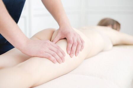 Closeup of the arm of a masseur male doing hip massage to a girl in a spa salon. Massage and body care concept