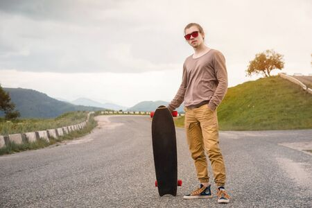 A stylish young man standing along a winding mountain road with a skate or longboard in his hands the evening after sunset. The concept of youth sports and travel hobbies