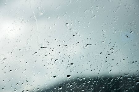 Fond naturel Gouttes des deux côtés du verre de la pluie et de la vue abstraite brumeuse, gouttes de pluie contre le verre bleu et le paysage flou du dégradé de bleu et de vert Banque d'images