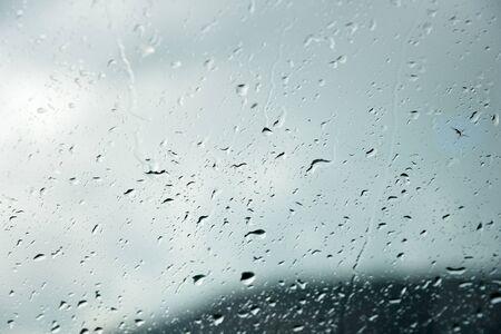 Natuurlijke achtergrond Druppels aan beide kanten van het glas door de regen en door het beslagen abstracte beeld, regendruppels tegen het blauwe glas en het wazige landschap van het verloop van blauw en groen Stockfoto