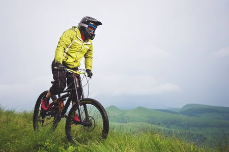 Front view of a man on a mountain bike standing on a rocky terrain and looking down against a gray sky. The concept of a mountain bike and mtb downhill