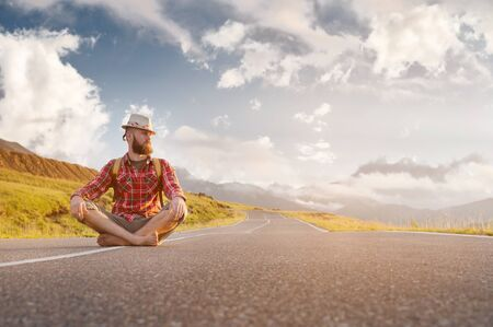 Stylish barefoot bearded male hitchhiker traveler in a hat and with a backpack sits on a suburban asphalt road in the mountains at sunset and waits for cash assistance looking to the sky. Reklamní fotografie