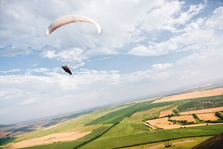 A paraglider flies in the sky in a cocoon suit on a paraglider over the Caucasian countryside with hills and mountains. Paragliding Sport Concept Stok Fotoğraf