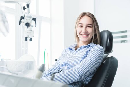 Portrait of an attractive smiling girl blonde in a dental chair. Happy customer dental cabinet Фото со стока