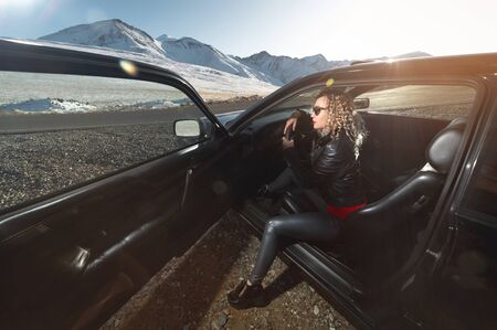 Fashion style wide angle young stylish attractive girl with bright red lips in a leather jacket and sunglasses sits in a retro 90s car with an open door on nature in the mountains at sunset