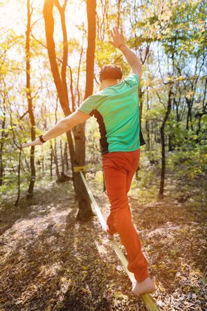 Wide angle male tightrope walker balancing barefoot on slackline in autumn forest. The concept of outdoor sports and active life of people aged.