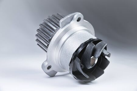 New metal automobile pump for cooling an engine water pump on a gray background with a gradient. The concept of new spare parts for the car engine.