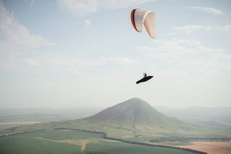 A paraglider flies in the sky in a cocoon suit on a paraglider over the Caucasian countryside with hills and mountains. Paragliding Sport Concept.