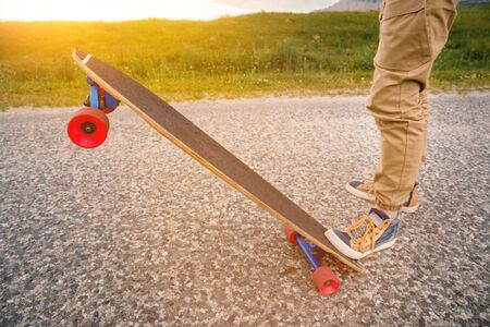 Close-up of male legs in rag sneakers on a longboard on the background of asphalt at sunset. Big skateboard with man legs. Youth leisure concept. 版權商用圖片 - 131853353
