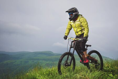 Front view of a man on a mountain bike standing on a rocky terrain and looking down against a gray sky. The concept of a mountain bike and mtb downhill. 版權商用圖片