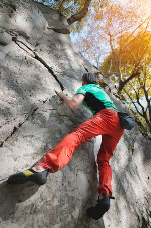 A free aged male climber hangs on a rock wall in a forest in the mountains. Mature Sports Concept.