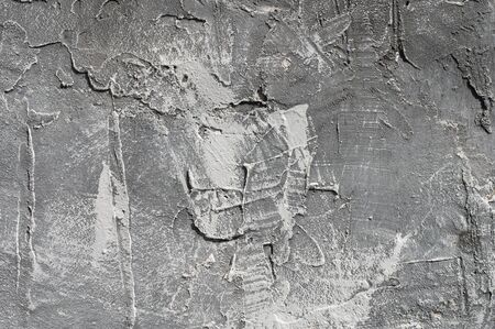The texture of gypsum or alibaster cracked plaster on the wall is a thick layer. Gradient gray putty wall background.