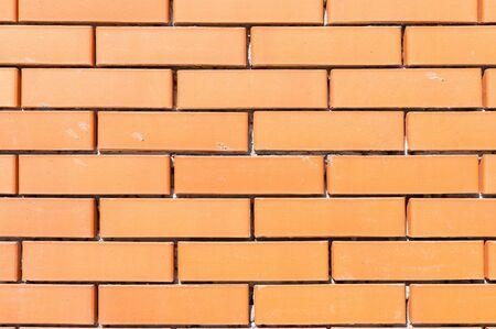 Textured background new brickwork close-up orange brick.