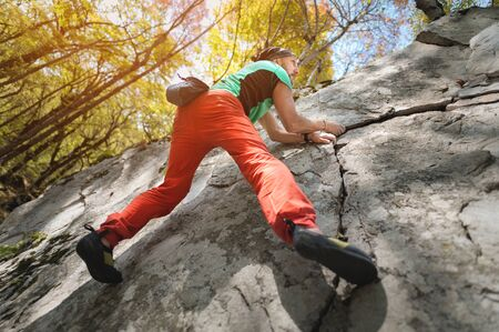 A free aged male climber hangs on a rock wall in a forest in the mountains. Mature Sports Concept Фото со стока