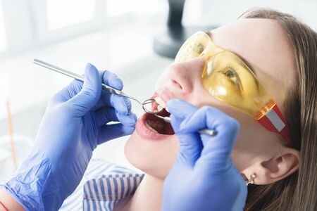 A close-up of the girls face is examined by a dental examiner with his mouth open and a napkin and eyes closed. Dentist hands with inspection tools.