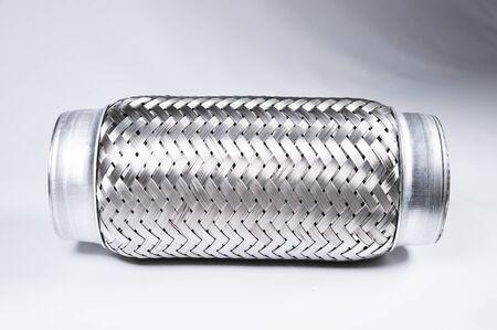Connexion flexible d'image à contraste complet au système d'échappement d'une voiture de tourisme sur un fond dégradé gris. Le concept de nouvelles pièces automobiles.