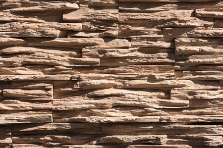 Abstract beige brown slate pattern stone block wall texture for background and wallpaper large and wide modern stone wall facade.
