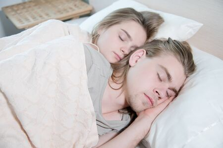 Close-up of a young couple in bed sleeping in an embrace, hiding behind a blanket. The concept of a young family and healthy sleep Stock Photo - 133219575