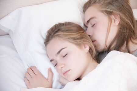 Close-up of a young couple in bed sleeping in an embrace, hiding behind a blanket. The concept of a young family and healthy sleep Stock Photo - 133224744