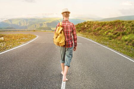 Stylish barefoot bearded male hitchhiker traveler in a hat and with a backpack walks along a suburban asphalt road in the mountains at sunset. The view from the back. Travel concept without money.