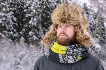 Portrait of an attractive manly man with a mustache and beard in a winter forest. Stylish tourist in a fur hat and a bright scarf Zdjęcie Seryjne