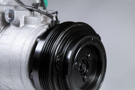 Primo piano Compressore dell'aria condizionata per auto nuove su sfondo grigio. Archivio Fotografico