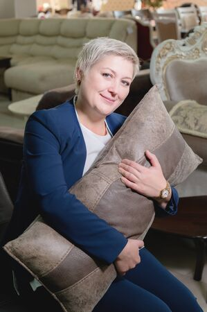Portrait of an adult short-haired blonde business woman in her furniture store sitting in an embrace with a pillow on a new brown sofa Banque d'images - 137188651