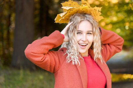 Portrait of attractive caucasian young blonde girl in red coat with a bouquet of fallen yellow leaves smiling in the autumn forest. The concept of autumn and fall holidays and weekends