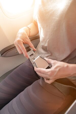 Close-up of a young woman fastens a seat belt while sitting in a passenger airplane chair by the window. The concept of safety measures for passenger flights in aircraft