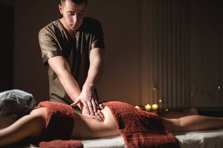 Professional premium massage in a dark atmospheric cabinet. Young man doing massage to a female client in a dark office on the background of burning candles