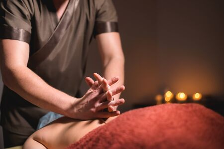 Close-up of the hands of a male masseur doing back massage to a girl at the spa. Low key high contrast shallow depth of field Reklamní fotografie
