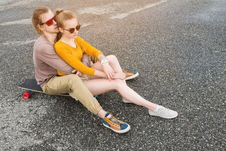 An attractive young couple in sunglasses sit back to back on their longboard in a suburban parking. The concept of a young family generation millennials style and leisure