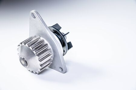 New metal automobile pump for cooling the engine of a water pump on a gray background. The concept of new spare parts for the car engine