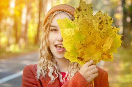 Portrait of attractive Caucasian young blonde girl in red coat in a red hat with a bouquet of fallen yellow leaves smiling in the autumn forest and covering her face with leaves.