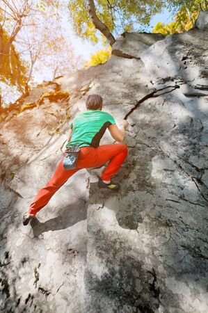 A free aged male climber hangs on a rock wall in a forest in the mountains. Mature Sports Concept Reklamní fotografie
