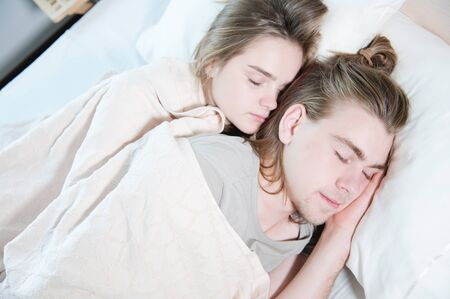 Close-up of a young couple in bed sleeping in an embrace, hiding behind a blanket. The concept of a young family and healthy sleep
