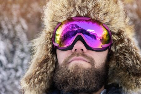 Close-up portrait of a bearded happy snowboarder skier in a ski mask with goggles and a fur big old-school hat on a background of a winter snowy mountains Reklamní fotografie