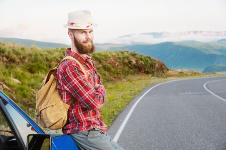Portrait of a bearded happy serious traveler hipster with a backpack in a plaid shirt and a hat next to an unknown car stands on the road at sunset in the mountains. Happy and confident travel concept