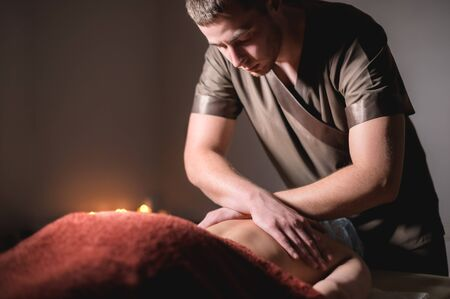 Close-up of the hands of a male masseur doing back massage to a girl at the spa. Low key high contrast shallow depth of field Banco de Imagens