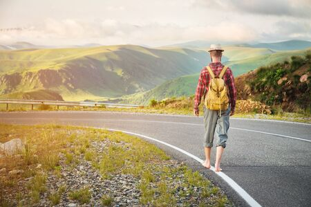 Stylish barefoot bearded male hitchhiker traveler in a hat and with a backpack walks along a country road in the mountains at sunset. The view from the back. Travel concept without money. 版權商用圖片