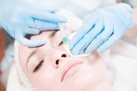 Close-up Attractive young woman gets anti-aging face injections. She lies calmly in a clinic or salon. An experienced young cosmetologist fills female wrinkles with hyaluronic acid from a syringe