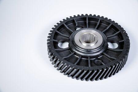 Árbol de levas de engranajes de polímero negro con base de metal. Nueva pieza de repuesto para un motor de combustión interna sobre un fondo gris