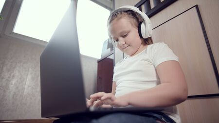 A smart little girl of seven years old in white headphones with a laptop in her hands is pushing on the floor in her room. The young generation on the Internet and IT technology Reklamní fotografie