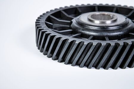 Black polymer gear camshaft with metal base. New spare part for an internal combustion engine on a gray background