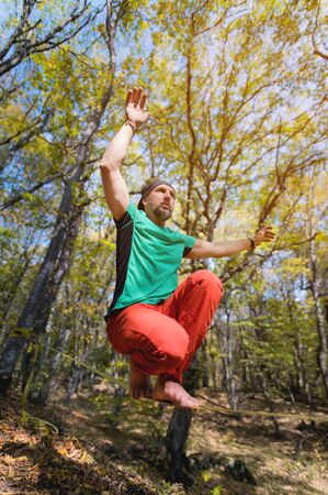 Wide angle male tightrope walker balancing while sitting barefoot on slackline in autumn forest. The concept of outdoor sports and active life of people aged