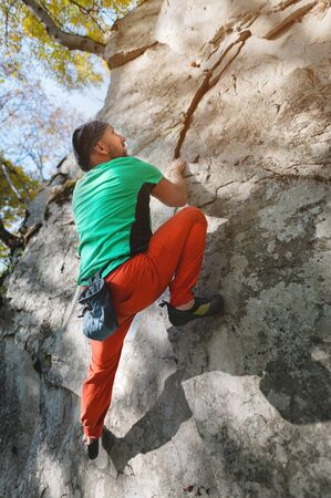 A free aged male climber hangs on a rock wall in a forest in the mountains. Mature Sports Concept Zdjęcie Seryjne