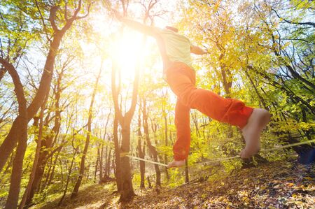 Wide angle male tightrope walker balancing barefoot on slackline in autumn forest. The concept of outdoor sports and active life of people aged